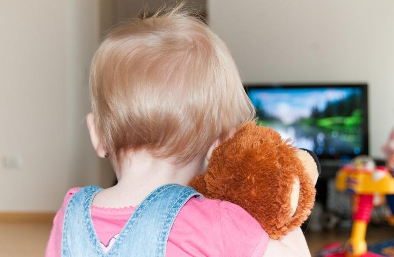 Ребенок смотрит телевизор с игрушкой в обнимку